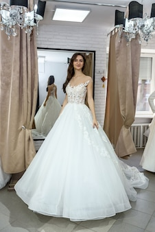 ウェディングドレスでポーズをとって若い笑顔の花嫁