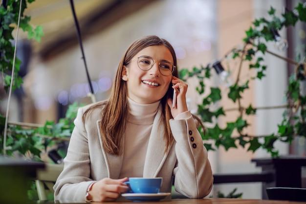 Молодая улыбающаяся брюнетка в элегантной повседневной одежде сидит в кафе, держит чашку кофе и разговаривает по телефону с другом.