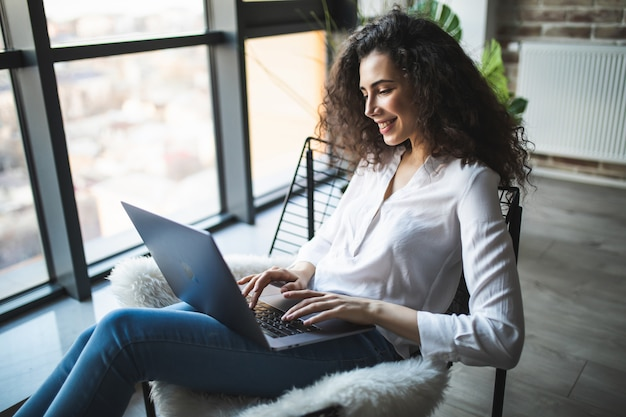 Young smiling brunette girl is sitting on modern chair near the window in light cozy room at home working on laptop in relaxing atmosphere