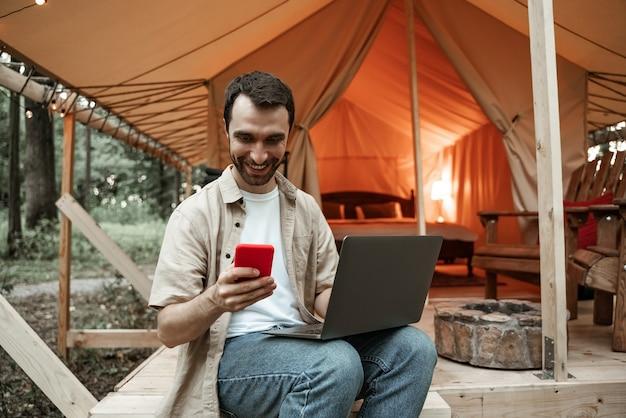 Молодой улыбающийся брюнетка человек, сидящий на глэмпинге, используя ноутбук и смартфон, потоковую передачу, обмен сообщениями. кемпинговый образ жизни. малобюджетные путешествия. концепция удаленной работы. современные коммуникационные технологии в интернете.