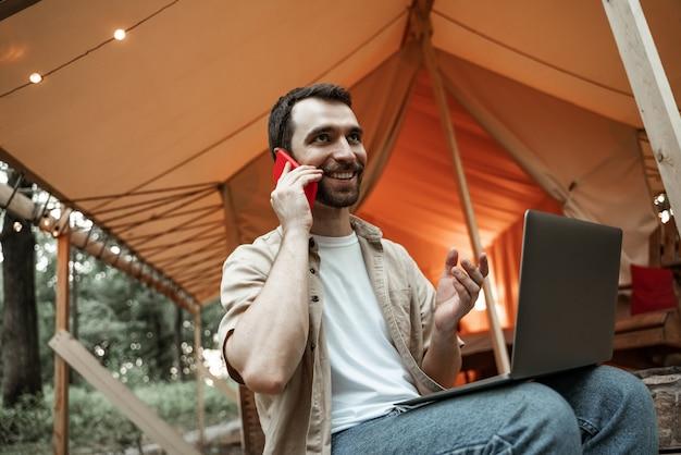 Молодой улыбающийся брюнетка человек, сидящий на глэмпинге, используя ноутбук, разговаривает на смартфоне, объясняя. кемпинговый образ жизни. малобюджетные путешествия. концепция удаленной работы. современные коммуникационные технологии в интернете.