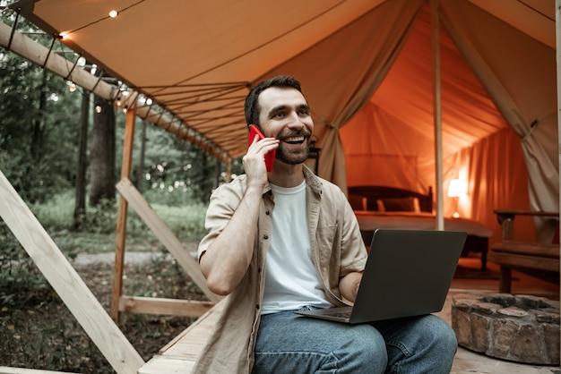 Молодой улыбающийся брюнетка человек, сидящий на глэмпинге, используя ноутбук, разговаривает на смартфоне, потоковая передача. кемпинговый образ жизни. малобюджетные путешествия. концепция удаленной работы. современные коммуникационные технологии в интернете.