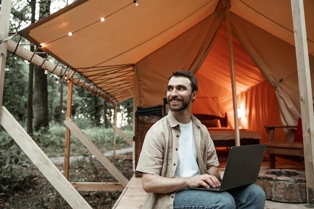 Молодой улыбающийся брюнетка человек, сидящий на глэмпинге, используя ноутбук, печатая, глядя на расстоянии. кемпинговый образ жизни. малобюджетные путешествия. концепция удаленной работы. современные коммуникационные технологии в интернете.