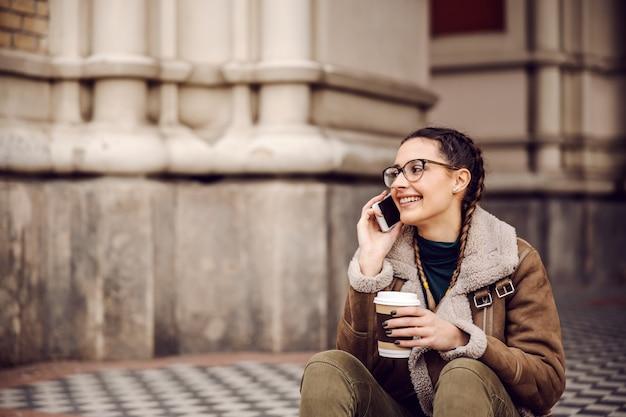 Молодая улыбающаяся брюнетка сидит на земле перед старым зданием, держит одноразовую чашку и разговаривает по телефону.