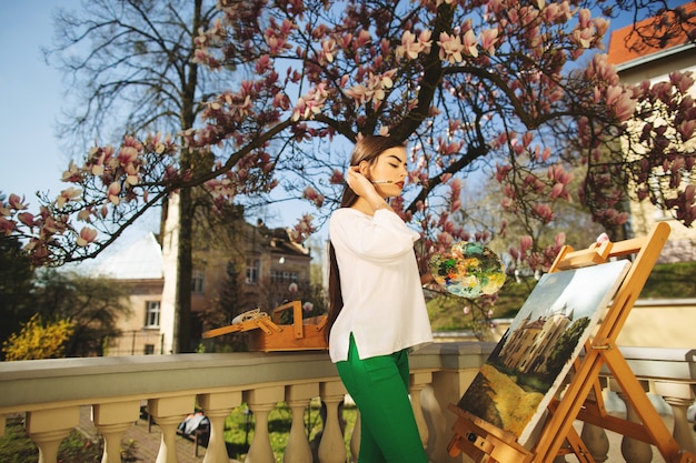 Young smiling brunette woman artist paints a picture on the street, near a beautiful tree of magnolia