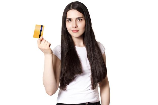 Молодая улыбающаяся брюнетка в белой футболке демонстрирует свою кредитную карту золотого банка для макета