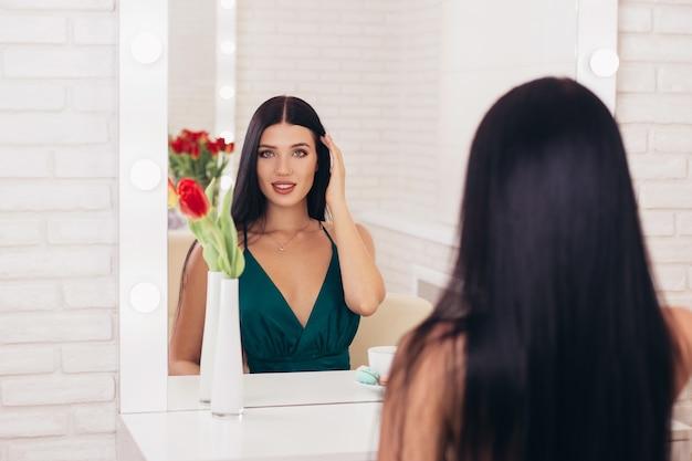 Молодая улыбающаяся брюнетка женщина с чашкой кофе, глядя в зеркало в парикмахерской