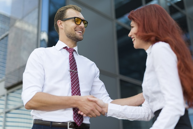 Young smiling business people shaking hands