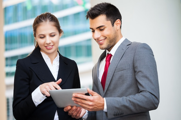 Young smiling business people using a digital tablet
