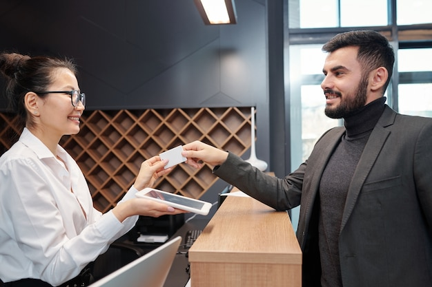 Young smiling business traveler taking card from hotel room by reception counter while looking at pretty receptionist