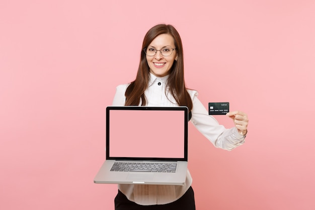 Young smiling business woman in glasses holding credit card, laptop pc computer with blank empty screen isolated on pink background. lady boss. achievement career wealth. copy space for advertisement.