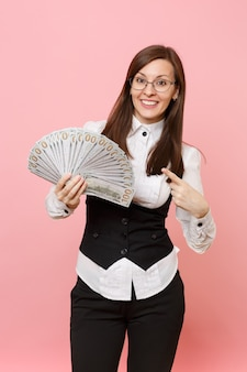 Young smiling business woman in glasses pointing index finger on bundle lots of dollars, cash money isolated on pink background. lady boss. achievement career wealth. copy space for advertisement.