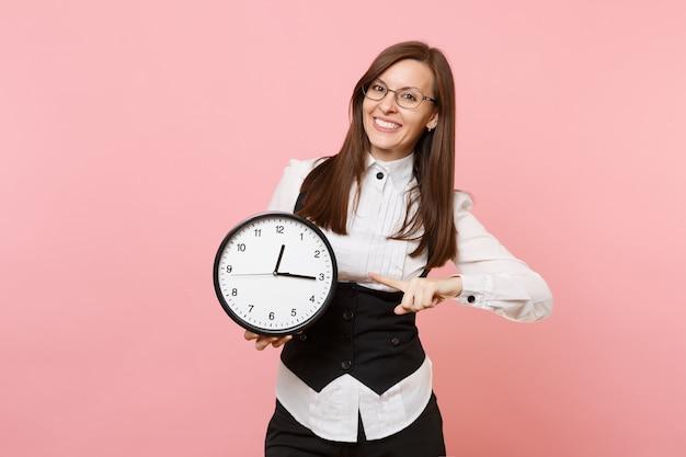 파스텔 핑크색 배경에 격리된 알람 시계에 검지 손가락을 가리키는 안경을 쓴 젊은 미소 비즈니스 여성. 여사장님. 성취 경력 부 개념입니다. 광고 공간을 복사합니다.