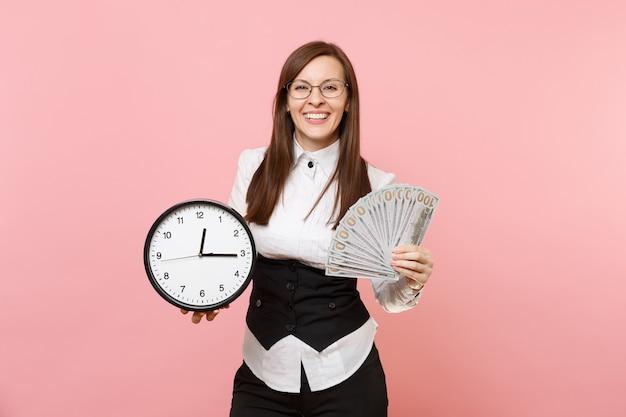 ピンクの背景に分離されたたくさんのドル、現金、目覚まし時計のバンドルを保持しているスーツのメガネで若い笑顔のビジネス女性。女上司。達成キャリアの富。広告用のスペースをコピーします。