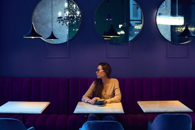 テーブルのカフェに座って、窓の外を見て若い笑顔ビジネス女性。テーブルの上にコーヒーがあります。