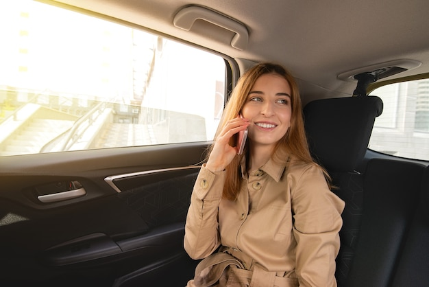 Young smiling business woman sitting on the rear passenger seat of her car and negotiating on the phone . business concept