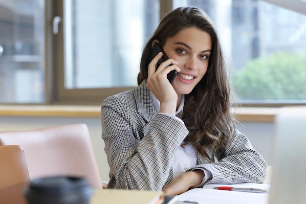 オフィスのコンピューターの近くでスマートフォンを使用して若い笑顔のビジネス女性。