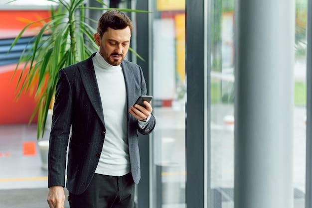 Молодой улыбающийся бизнесмен, позвонив по телефону в офисе.