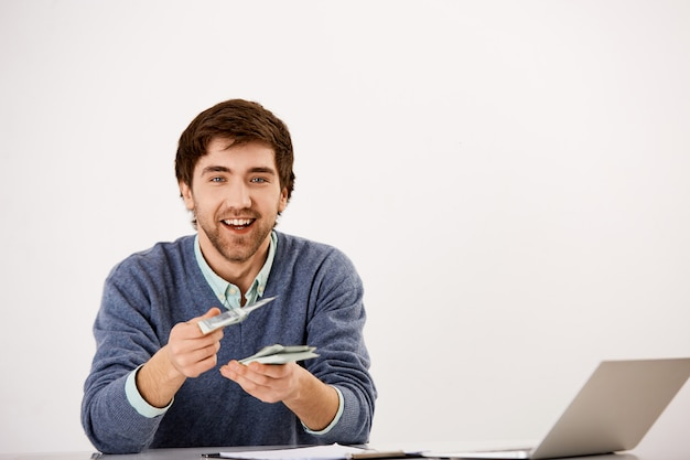Young smiling businessman give cash, sit at desk with laptop, counting money, give half of income to business partner