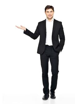 Il giovane uomo d'affari sorridente tiene qualcosa sul palmo isolato su bianco.