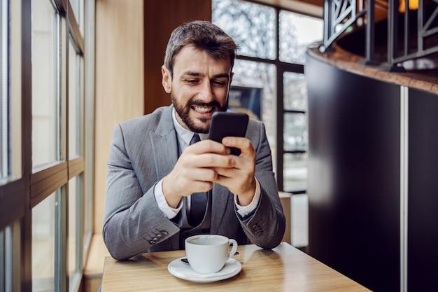 コーヒーブレークのコーヒーショップに座っているとスマートフォンでメッセージを入力して笑顔の若手実業家。