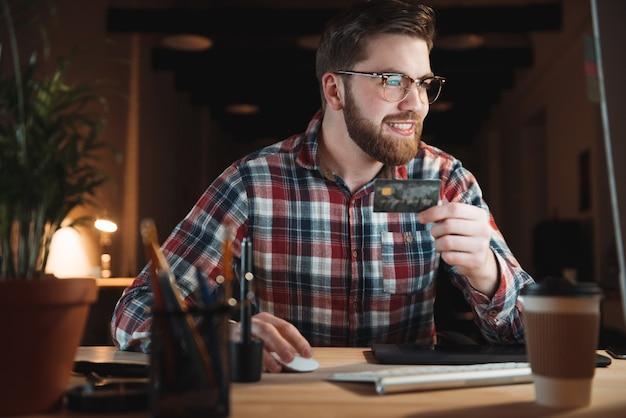 Молодой улыбающийся бизнесмен с компьютером и кредитной картой, делающей покупки онлайн в офисе
