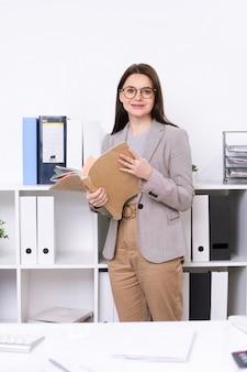 Молодая улыбающаяся деловая женщина в элегантной повседневной одежде, держащая коллекцию документов, стоя в офисе