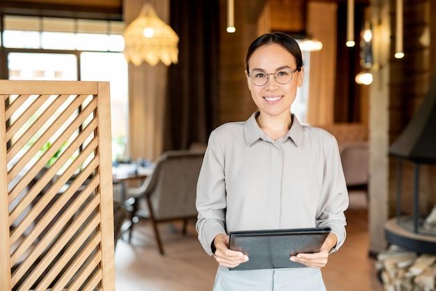 Молодой улыбающийся бизнесмен азиатской национальности, держащий документ, стоя в роскошном ресторане