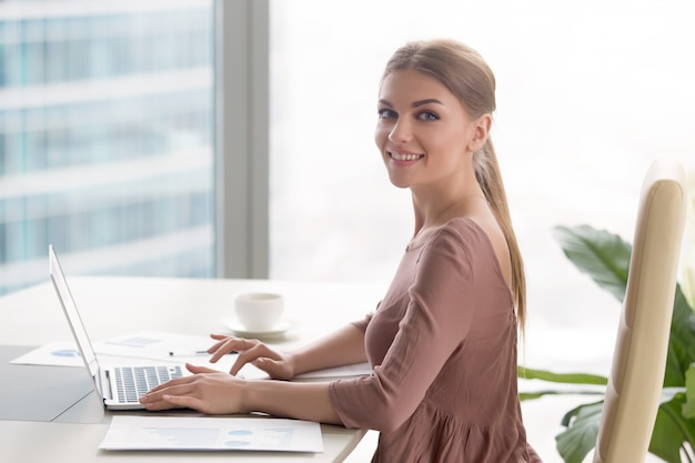 Young smiling businesswoman sitting at office desk looking at camera