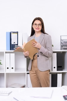 Young smiling businesswoman in smart casualwear holding collection of documents while standing in office
