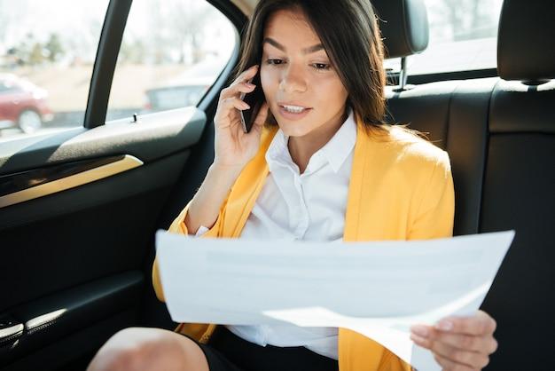 Молодая улыбающаяся деловая женщина разговаривает по телефону