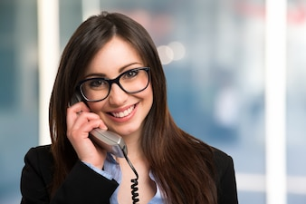 Young smiling businesswoman talking on the phone