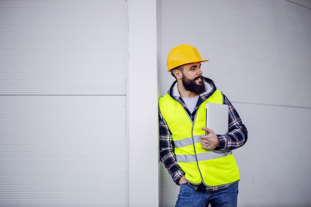 Young smiling caucasian bearded construction worker with helmet on head in vest leaning on the wall, holding laptop in hands and looking at other workers.