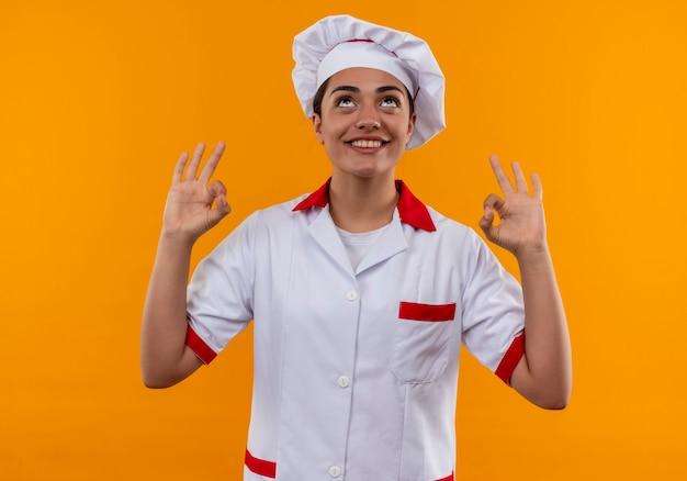 La giovane ragazza caucasica sorridente del cuoco nel segno giusto della mano di gesti dell'uniforme del cuoco unico e cerca isolata sulla parete arancio con lo spazio della copia
