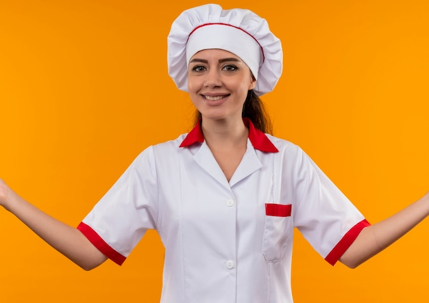Young smiling caucasian cook girl in chef uniform holds hands open isolated on orange wall with copy space