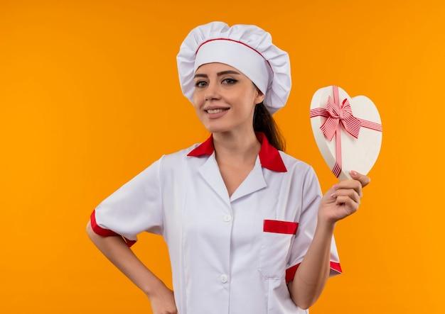 La giovane ragazza caucasica sorridente del cuoco in uniforme del cuoco unico tiene la scatola di forma del cuore isolata sulla parete arancione con lo spazio della copia
