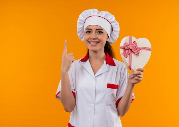 La giovane ragazza caucasica sorridente del cuoco in uniforme del cuoco unico tiene la scatola di forma del cuore e indica in su isolata sulla parete arancione con lo spazio della copia
