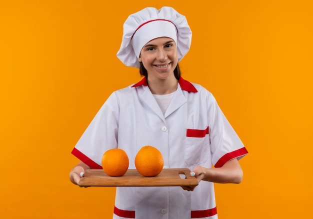 Young smiling caucasian cook girl in chef uniform holds oranges on cutting board isolated on orange space with copy space
