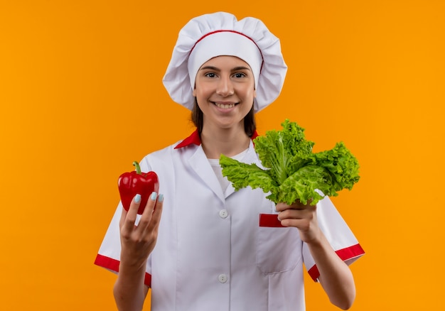 Young smiling caucasian cook girl in chef uniform holds red pepper and salad isolated on orange space with copy space