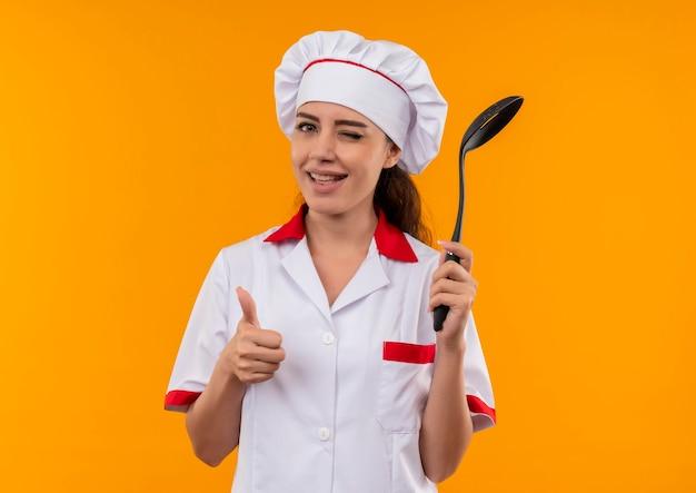 シェフの制服を着た若い笑顔の白人料理人の女の子がまばたき目を持ってへらと親指をコピースペースでオレンジ色の壁に隔離