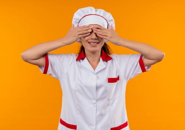 요리사 유니폼에 젊은 웃는 백인 요리사 소녀 복사 공간 오렌지 벽에 고립 된 손으로 눈을 감고