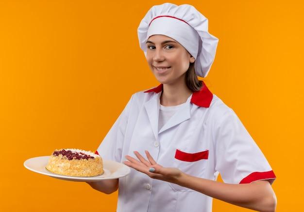 Молодая улыбающаяся кавказская девушка-повар в униформе шеф-повара держит и указывает на торт на тарелке, изолированной на оранжевом пространстве с копией пространства