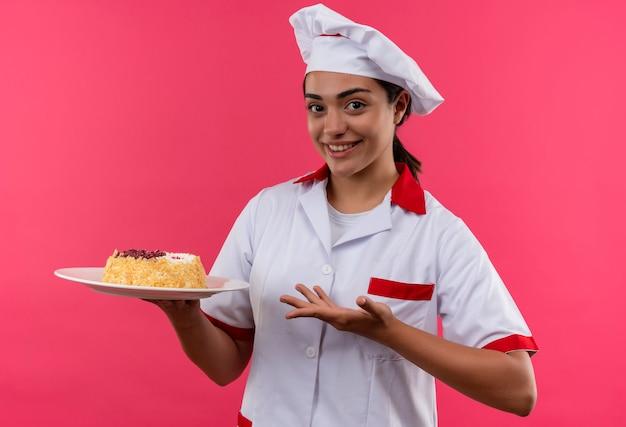 Молодая улыбающаяся кавказская девушка-повар в униформе шеф-повара держит торт на тарелке и указывает рукой, изолированной на розовой стене с копией пространства