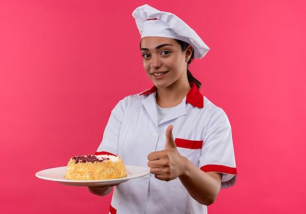Молодая улыбающаяся кавказская девушка-повар в униформе шеф-повара держит торт на тарелке и показывает палец вверх, изолированную на розовой стене с копией пространства