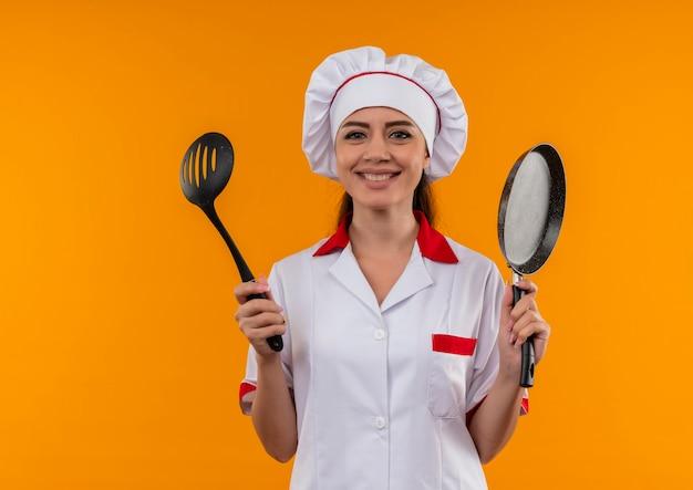シェフの制服を着た若い笑顔の白人料理人の女の子は、コピースペースでオレンジ色の壁に分離されたフライパンとヘラを保持します。