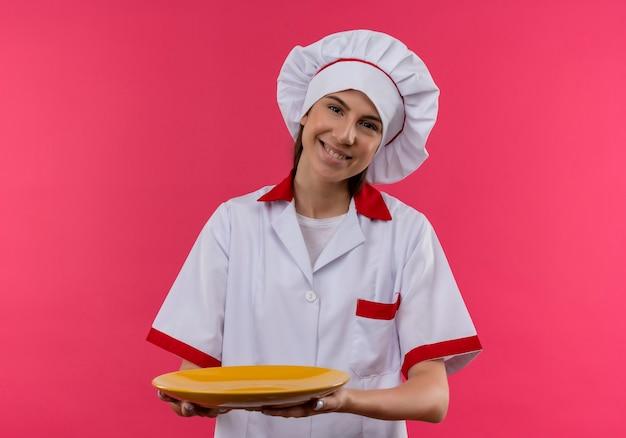 シェフの制服を着た若い笑顔の白人料理人の女の子は、コピースペースとピンクのスペースで隔離のプレートを保持します