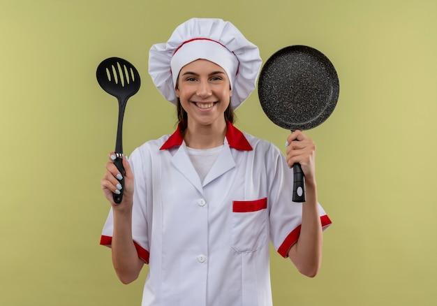 シェフの制服を着た若い笑顔の白人料理人の女の子は、コピースペースと緑のスペースに分離されたヘラとフライパンを保持します。