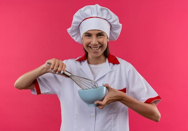 シェフの制服を着た若い笑顔の白人料理人の女の子は、コピースペースでピンクの泡立て器とボウルを保持します
