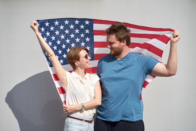 Young smiling caucasian couple of americans holding usa flag behind and looking at each other