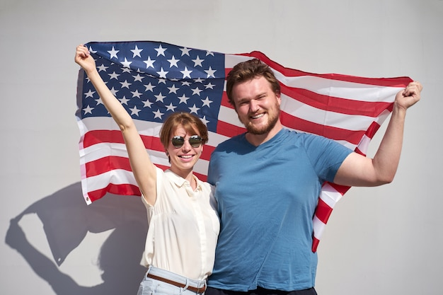 Young smiling caucasian couple of americans holding usa flag behind, sunny summer weather, gray background